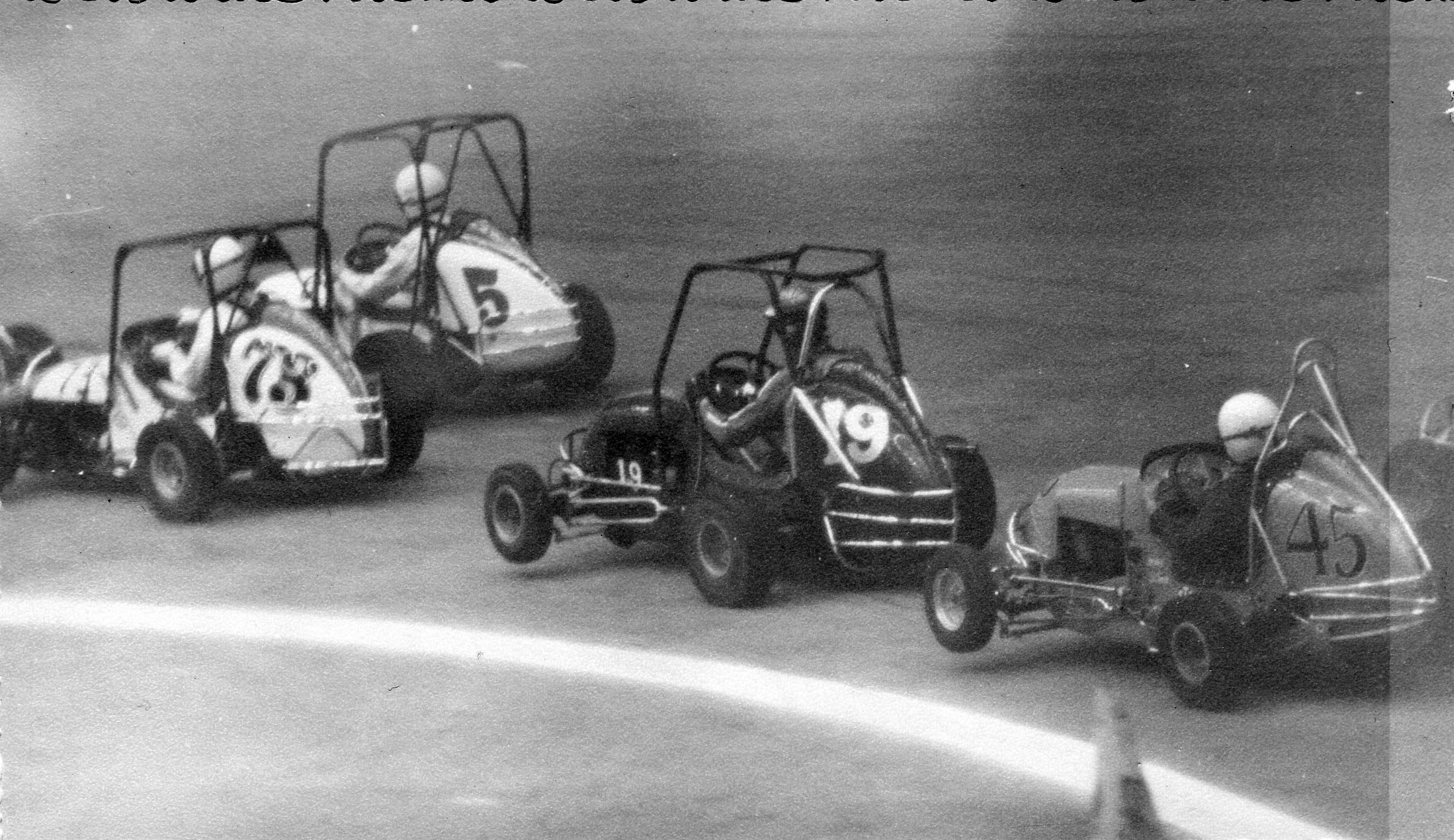 January 23, 1971 -- 73 Jack Bertling, 5 Jerry Wall, 19 Paul Weisel, Jr., 45 Len Duncan, 8-time ARDC midget champion. Everyone's hiking the left front coming off turn two. Source: EARHS