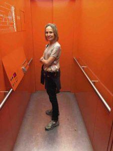 carol in orange elevator